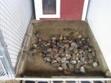 The first 2 loads we use small to medium sized river rock and then spread that out evenly in the kennel.