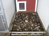The last 2 loads of river rock are large rocks.  This discourages dogs from digging.  If they're able to dig down to this level they'll hit large river rock and will immediately lose interest.